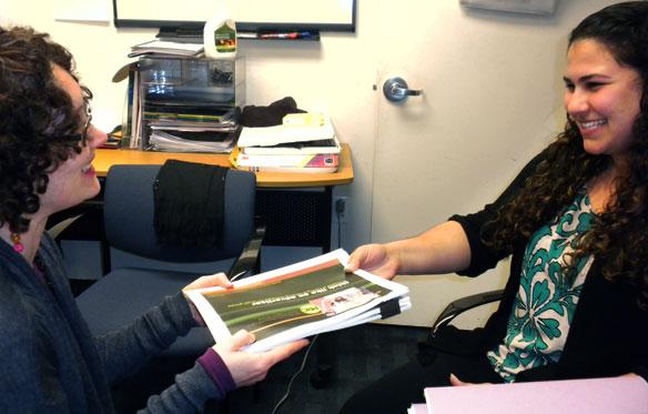 My supervisor, Carly Hutchinson, handing me health literacy documents.